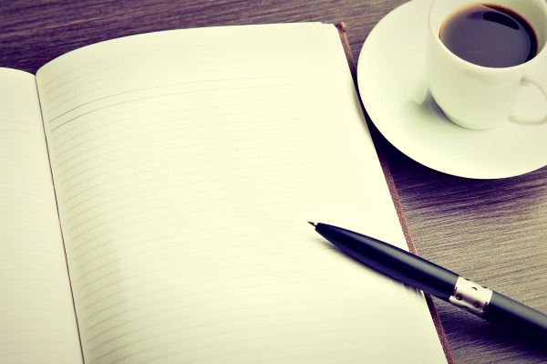 blank open notebook with pen and coffee cup